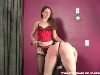 Naughty slave is bent over so Mistress can use her crop his ass