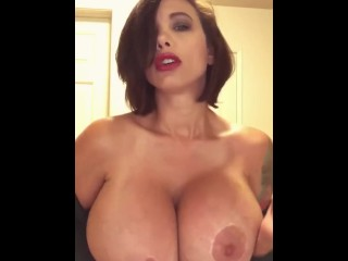 Amazing busty brunette rubs her huge fake tits